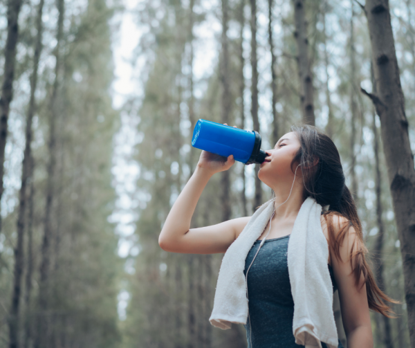 woman drinking out of water bottle in forest